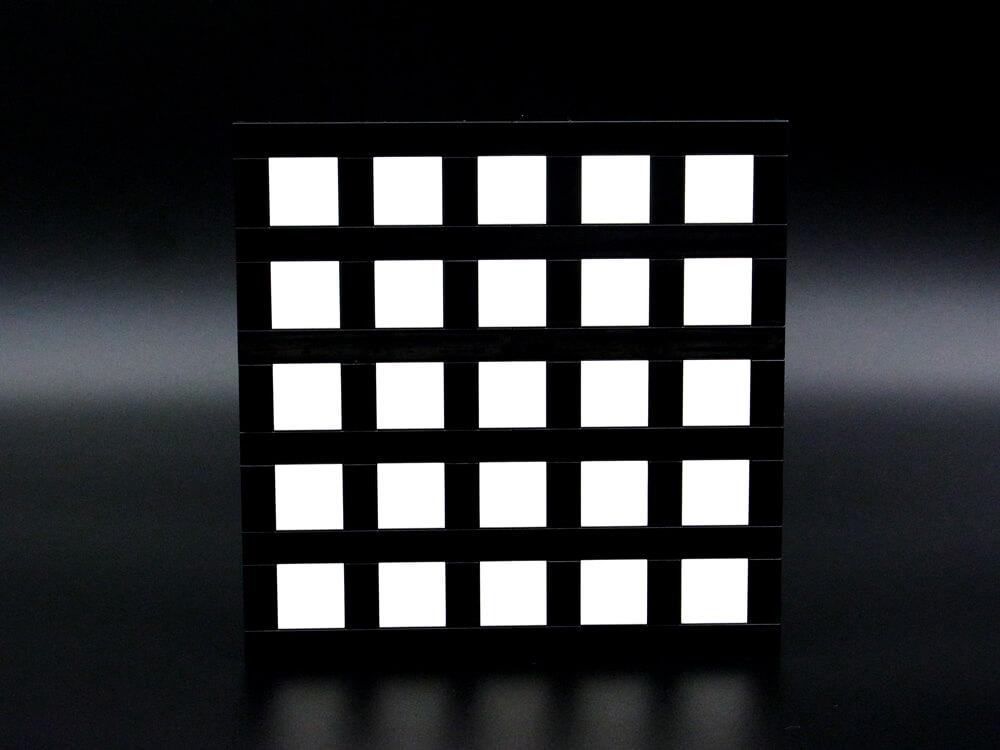 ヘルマン格子錯視のレゴ作品。白い四角タイルに張り巡らされた黒いタイルの交差点が明るく見えます。