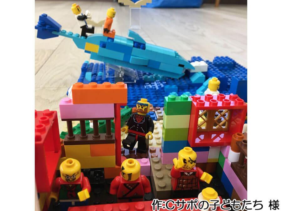 子どもたちによる海水浴の作品。海の家の向こうには、大きなイルカが見えます。